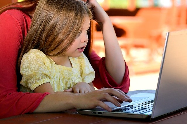 A parent and kid using a computer