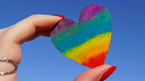 A close-up of a rainbow-painted heart being held in a person's hand against a clear blue sky.